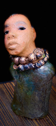 """It is obvious Herdew implies that most of my sculptures are female. My goal this year is to create ten male sculptures. Alvin is one of the first that I am pleased with. Alvin stands 9"" x 4"" x 4"" and weighs 2.13 lbs. He wears a metallic multi colored jacket with metallic beads. Alvin has a dark honey brown complexion. Alvin seems to be in deep thought. Alvin  would display proudly in your home."