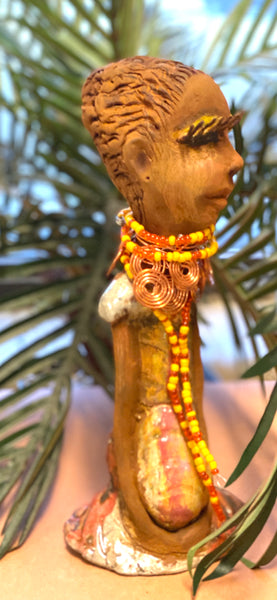 Reandra has a colorful reddish metallic green antique copper glazed dress. She wears a spiral copper wire necklace on top of a yellow red beaded collar. With eyes slightly opened, Reandra has hopes of finding a new home.