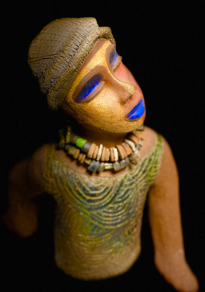 "Meet Blue! Blue stands 18"" x 14"" x 5"". She weighs 6 lbs. Blue has a multicolored face, blue lips and eye shadow. He also has a tribal symbol on his cheek.  A string of raku beads wraps around his neck. Blue struts a carved asymmetrical pattern throughout his top. Very Exotic & Eccentric!"
