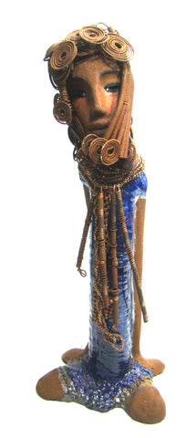 "Kya stands 20"" x 8"" x 5"" and weighs 6.04 lbs.     She has a lovely honey brown complexion.     Kya has over 40 feet of rust wire coils and spiral hair.     Her dress is a metallic blue with streaks of copper.     Her necklace is made from rust wire coils and amber beads.     Kya has long loving arms that are placed behind her.     Kya radiates like a blue diamond in the sky.     Give Kya a special place in your home!     Free Shipping!"
