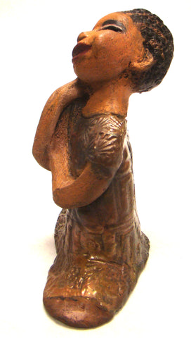 "Rae stands 8"" x 6"" x 3"" and weighs 1.09 lbs.     Rae has a beautiful spirit. She has a honey brown complexion.     Her long loving arms are nestled under her face as she gazes.     Her braids are made of clay.     Rae wears a metallic copper dress.     Rae is adorable and deserves a prominent place in your home."