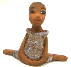 "Wanda stands  6"" x 6"" x  2.5"" and weighs  9 ozs.     She has a honey brown complexion with black inked in spiral hair.     Her dress is textured with a blue and gold metallic glaze.     Wanda sits in a yoga pose with her long loving arms at her side.     Give Wanda a special place in your home."