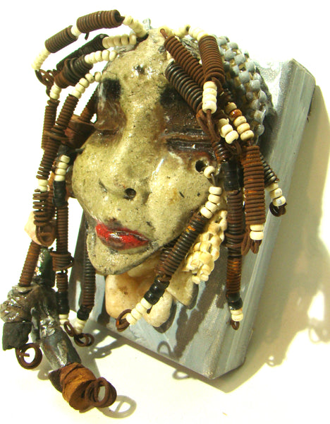 "This mask charm and mystic appeal is a keeper. 4"" x 6"" x 1.5"" canvas painted soft gray. Raku fired mask with white crackle glazes. The hair is made of  handmade beads and over 20 feet of  wire coils. Ready to be hung!"