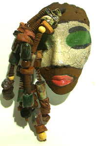 "These is a nice little mask that has red lips, white crackle, green eyes, and a rust brown face.      Has over 30 raku and wood beads.     Rust Coils     4"" x 6""     15 ozs     Back Hook"
