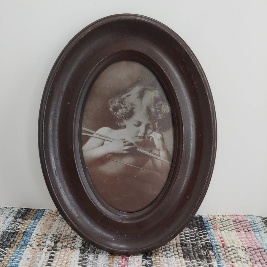 Ohio art company, sleeping cupid in metal oval frame