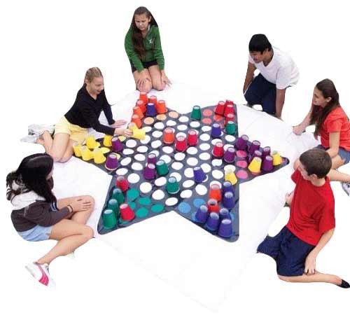 six people playing a giant game of chinese checkers sitting down