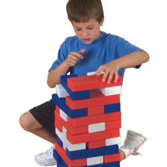 boy in blue shirt playing with timber red, white and blue tumbling blocks