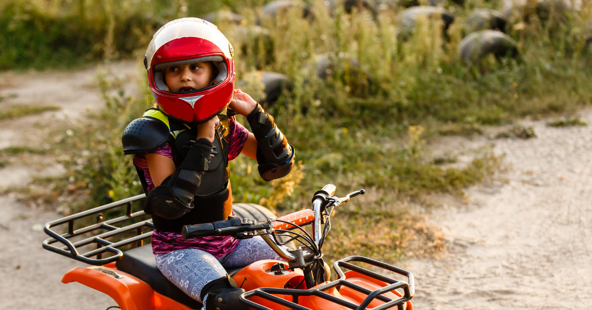 Boy wearing safety gears while quad riding