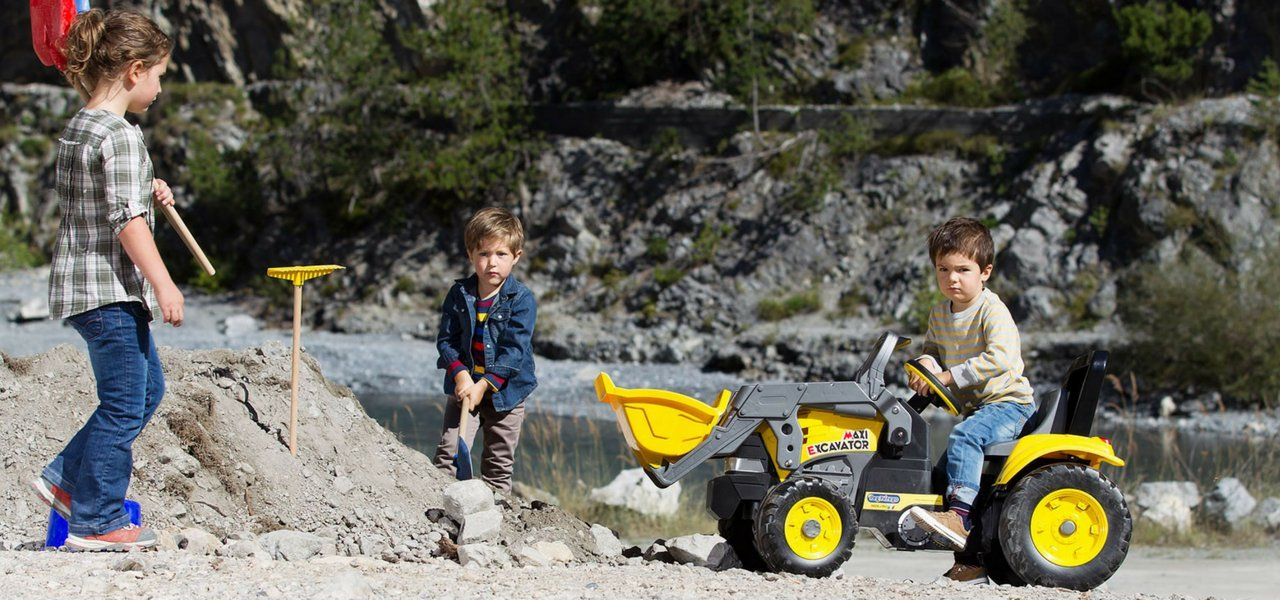 Three boys with ride on kids tractor at river digging in the dirt