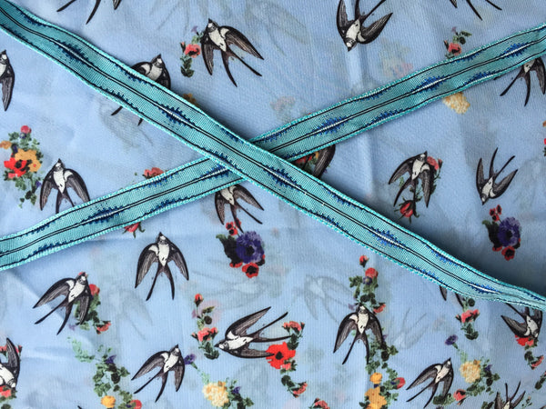 Swallows over the garden with turquoise ribbon