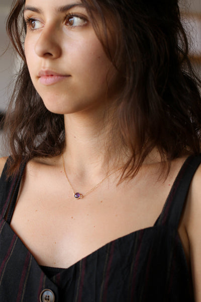 Short, wavy, brown haired model wearing a genuine amethyst gold necklace - MaeMae Jewelry