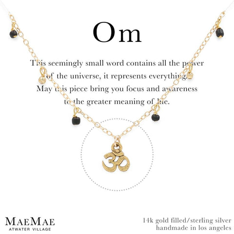 Gold bracelet with small dangling gold balls and small black beads with a dainty om symbol charm on a positive affirmation card - MaeMae Jewelry