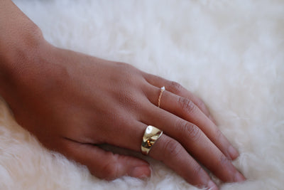 Close up picture of a model's hand wearing a gold statement ring and a dainty chain ring - MaeMae Jewelry
