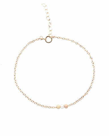 14k gold filled bracelet with tricolored stardust beads on white background