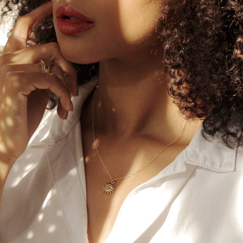 Model wearing a MaeMae 14K Gold Filled Light After Dark Neklace with a gold Sun Moon Charm. L