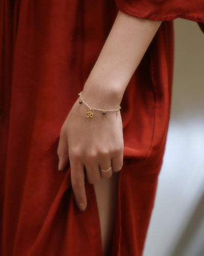 Model in a red dress wearing a gold bracelet with a small om charm and dangling beads - MaeMae Jewelry