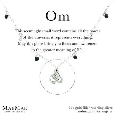 Silver bracelet with small dangling gold balls and small black beads with a dainty om symbol charm on a positive affirmation card - MaeMae Jewelry