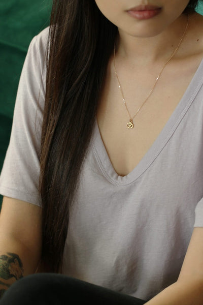 Model in a lavender shirt wearing a gold chain necklace with a small om pendant - MaeMae Jewelry