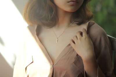 Model wearing 14k gold filled chain with gold plated pewter bandaid charm - MaeMae Jewelry