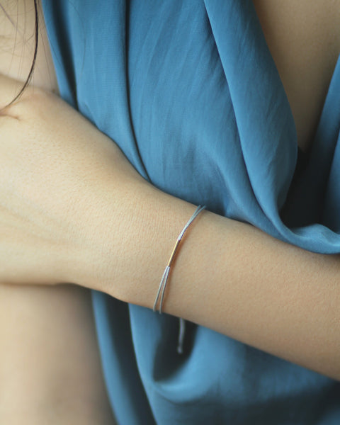 Model wearing adjustable silver nylon cord bracelet with 14k gold filled bar - MaeMae Jewelry