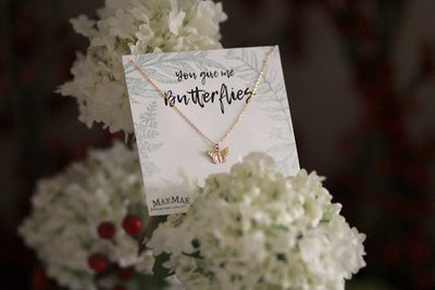 Lifestyle photo of 14k gold filled dainty butterfly pendant on chain necklace that comes with an illustrated square card - MaeMae Jewelry