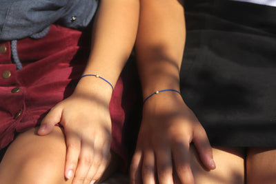 Lifestyle Models wearing I am priceless cord bracelets in blue MaeMae Jewelry friendship bracelets