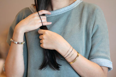 Woman in green shirt tying her hair with the hair tie bangle - MaeMae Jewelry