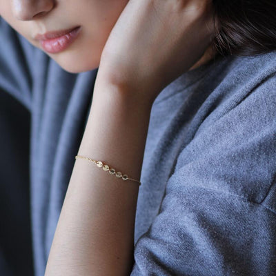 Girl wearing 14k gold filled cable chain bracelet with 5 golden discs.