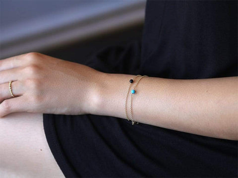 Lifestyle Photo Model Wearing Dainty Stone Bracelets in Gold - MaeMae Jewelry - Stack of Two - Turquoise and Black Onyx