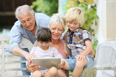 family with children and grandparents reading