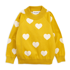 Girl's yellow knitted sweater with white heart patterns from Mini Rodini. Wide ribbed collar, cuffs, and waistband. It has a loose fit silhouette.
