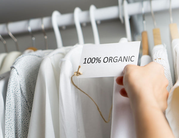 White Robes hanging from rack with Hand pulling on card showing label that says 100% Organic. Great for GOTS or OEKO-TEK Standard 100 which is a certificate for high quality and organic and ethical clothing. Found in Designer Children Kids' Wear