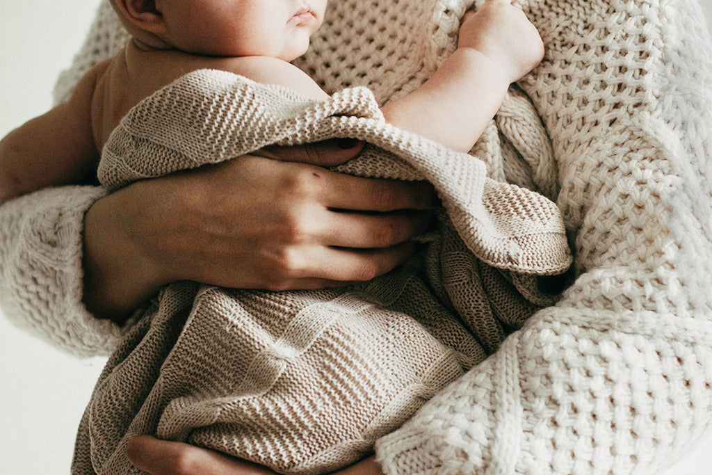 baby wrapped in neutral color organic blanket