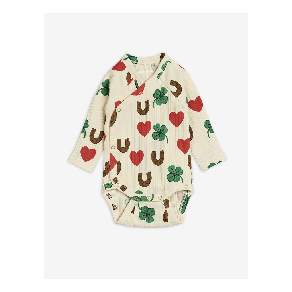 Organic beige cotton baby bodysuit. Patterned with red hearts, green clovers, and brown horseshoes all-over.