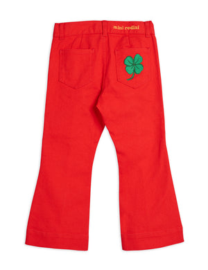 Red denim pants inspired by the 70s with a distinctive green four-leaf clover embroidered patch on the back.