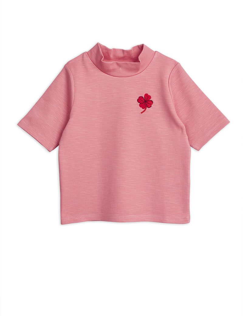 An adorable short-sleeved top in pink designed with a high neck. Small embroidered clover at the front.