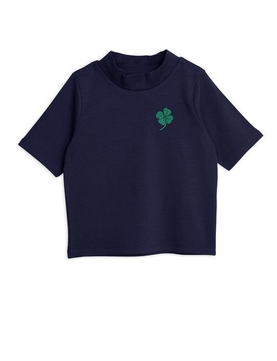 An adorable short-sleeved top in navy designed with a high neck. Small embroidered clover at the front.