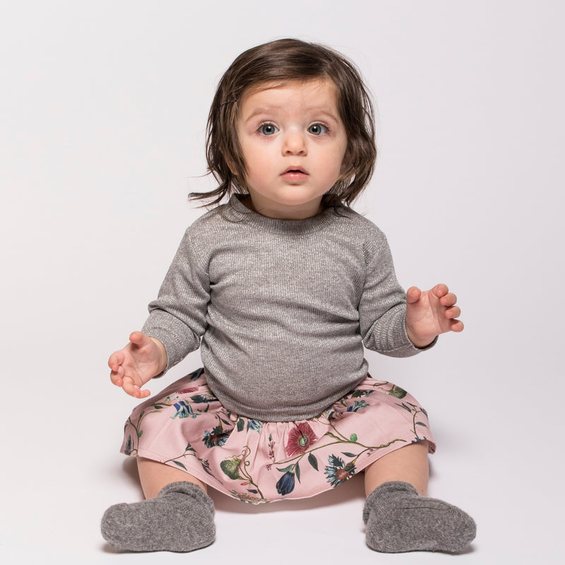 Baby wearing Designer Christina Rohde's light grey long sleeve sparkling top for babies