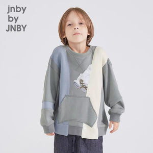 Boy model wearing a beautiful mono toned palette sweater in an artistic paneling style, this is a one of a kind kids designing clothing piece.
