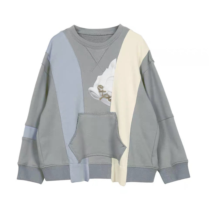 A beautiful mono toned palette sweater in an artistic paneling style, this is a one of a kind kids designing clothing piece.