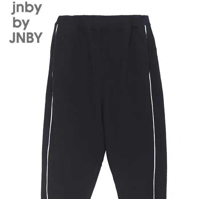 Black joggers with cuffed ankles and minimalist white lines running down the side. Designed by JNBY