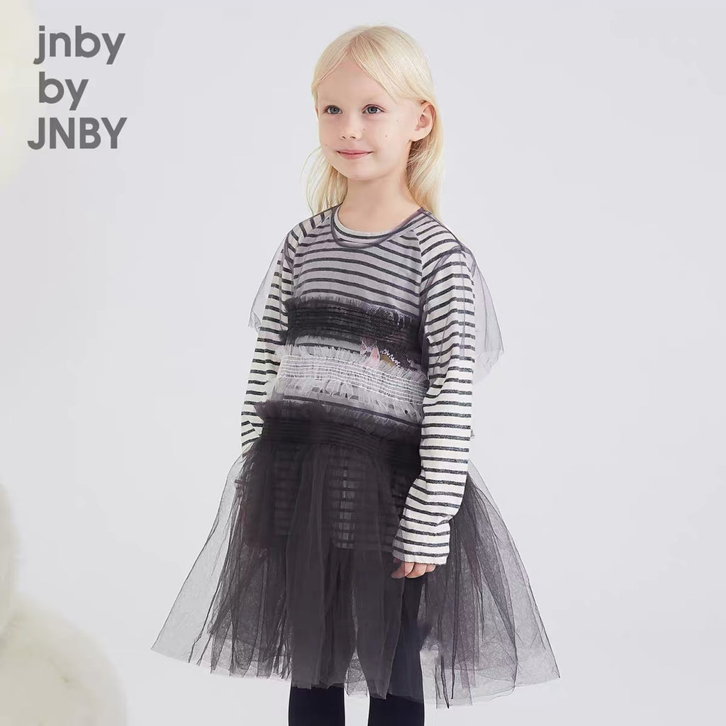 This is the go-to party dress layering piece. Fall in love with the elegant black tulle with delicate ruffle trims, making this dress for young girls look sweet but not childish. Designed by JNBY