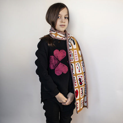 "A girl wearing black sweater is printed with a red heart in the shape of a four-leaf clover, with scallop trim on the sleeves. ""we love you"" printed at the back, and ribbed trim on the neckline, cuffs, and hem."