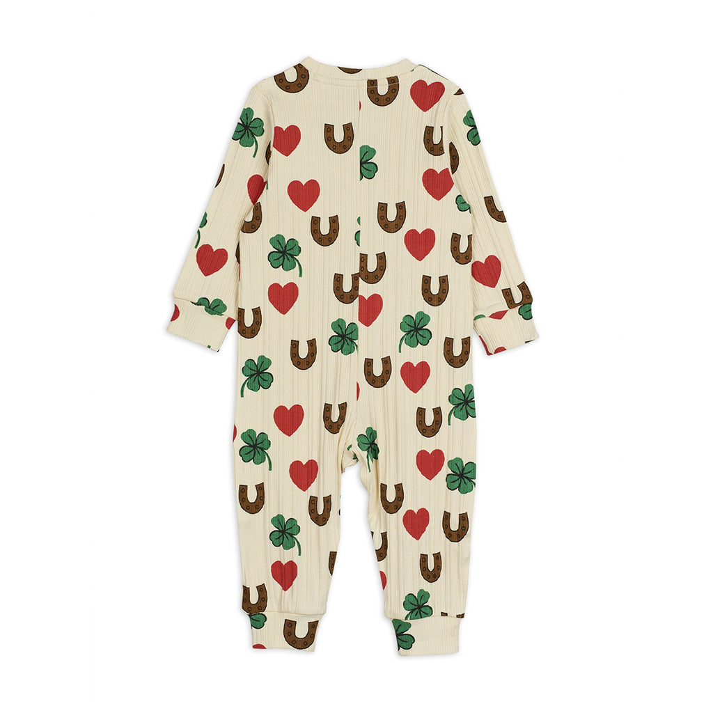Back of cute ivory organic cotton baby jumpsuit with red hearts, green clovers, and brown horseshoe print all-over. A design full of lucky charms for your young one.