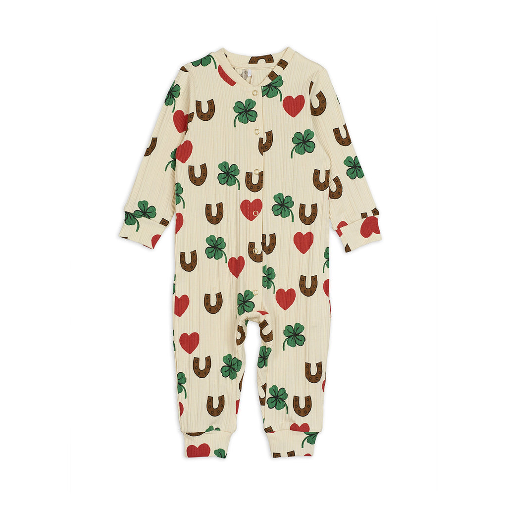 Cute ivory organic cotton baby jumpsuit with red hearts, green clovers, and brown horseshoe print all-over. A design full of lucky charms for your young one.