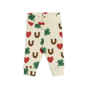 Ivory cotton baby leggings with red hearts, green clovers, and brown horseshoes print all-over. Cute love and lucky charm symbols for your young one.