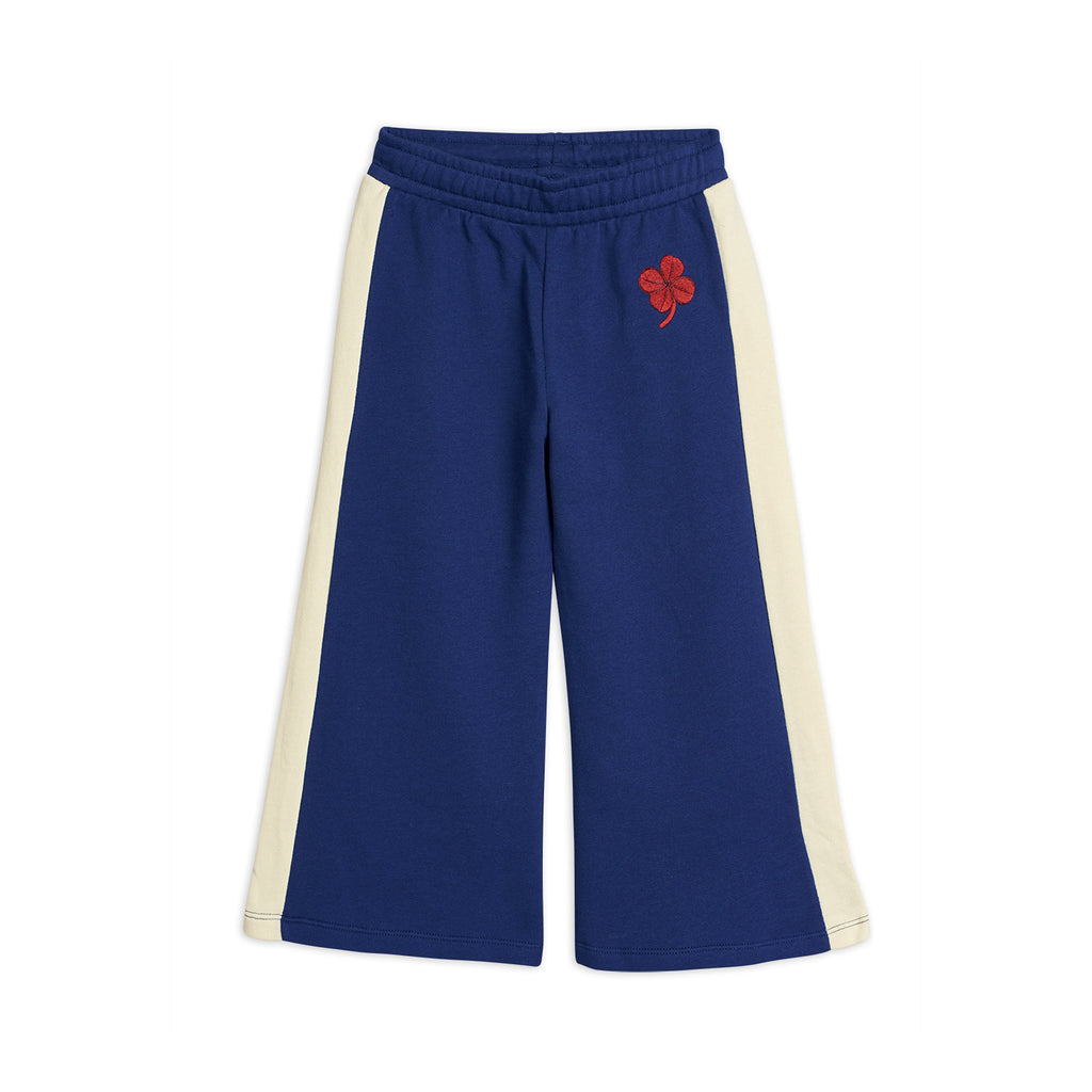 Comfortable blue cotton track pants with a wide fitting leg shape and green four-leaf clover embroidery at the front.