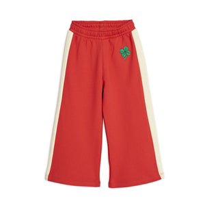 Comfortable red cotton track pants with a wide fitting leg shape and green four-leaf clover embroidery at the front.