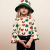 Girl model wearing Boys and Girls Organic Cotton Long Sleeve Shirt with red hearts, green clovers, and brown horseshoe print, along with matching hat. Designed by Mini Rodini