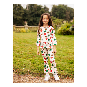 Female model wearing Mini Rodini long sleeve shirt with horseshoe, hearts, and clover print, with matching pants.